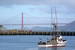 Bateau de pêche dans le quai de pêcheur contre golden gate bridge i Photographie stock libre de droits