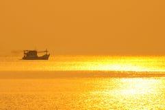 Bateau de pêche dans le temps de coucher du soleil Photo stock