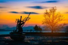 Bateau de pêche de silhouettes et arbre au temps de coucher du soleil, Phuket Photo stock