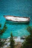 Bateau de pêche en bois blanc dans la baie avec de l'eau azuré de la mer Méditerranée Arbres de cyprès en pierre blancs de rivage Photos libres de droits