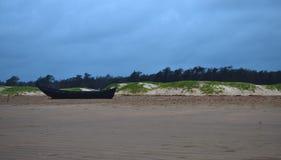 bateau de pêche en bois solitaire à la plage de mer avec une plage et des pins de sable image libre de droits