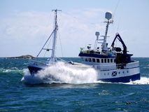 Bateau de pêche en cours à la vague de rupture de vitesse images stock
