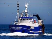 Bateau de pêche en cours en mer images stock