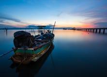 Bateau de pêche en mer au coucher du soleil Image stock