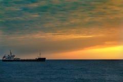 Bateau de pêche en mer ouverte sur l'horizon pendant le coucher du soleil Photos libres de droits