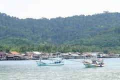 Bateau de pêche en mer près de village de pêcheurs photographie stock