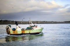 Bateau de pêche entrant dans le port Photos libres de droits