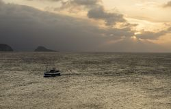 Bateau de pêche entrant pendant le coucher du soleil, au port d'Aviles photos libres de droits
