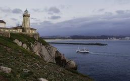 Bateau de pêche entrant pendant le coucher du soleil, naviguant devant le phare du saint Juan, au port image libre de droits