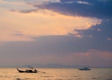 Bateau de pêche et bateau de vitesse en mer sur le fond de coucher du soleil Photos libres de droits