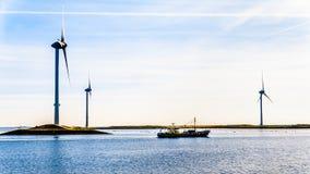 Bateau de pêche et turbines de vent à l'admission d'Oosterschelde à l'île de Neeltje Jans dans la province de Zélande aux Pays-Ba photos libres de droits