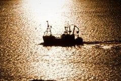 Bateau de pêche fonctionnant pendant le coucher du soleil Images stock