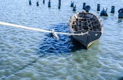 Bateau de pêche gris attaché avec une corde dans l'eau bleu-vert photographie stock libre de droits
