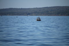 Bateau de pêche lointain de tir sur l'eau avec le rivage dans l'horizon Photos libres de droits