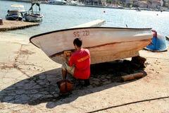 Bateau de pêche de peinture d'homme dans le port Photo stock