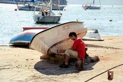 Bateau de pêche de peinture d'homme dans le port Images stock