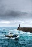 Bateau de pêche sous la tempête arrivant au pilier Image stock