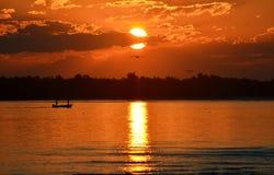 Bateau de pêche sur l'eau au coucher du soleil Photos stock