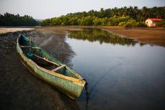Bateau de pêche sur la berge dans les tropiques avec des palmiers le soir, image stock