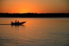 Bateau de pêche sur le fleuve de coucher du soleil Images stock