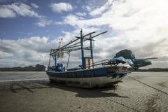 Bateau de pêche traditionnel s'étendant sur une plage près de la mer avec le nuage et le ciel bleu à l'arrière-plan, style coloré Photos stock