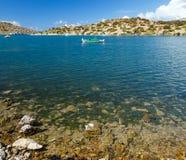 Bateau de pêche traditionnel sur l'eau de mer clair comme de l'eau de roche azurée dans la baie de l'île de Simi, Grèce images libres de droits