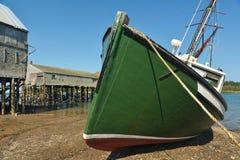 Bateau de pêche vert s'étendant sur la marée basse latérale Image stock