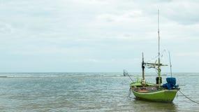Bateau de pêche vert simple flottant sur la mer le matin attendant à la voile dans l'océan la pêche de début par le pêcheur, Floa image libre de droits