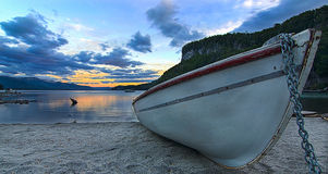 Bateau de pêcheur au coucher du soleil dans le lac photos stock
