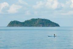 Bateau de pêcheur avec l'île Images stock