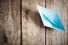 Bateau de papier bleu sur le vieux fond en bois Photographie stock libre de droits