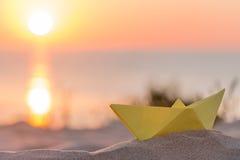 Bateau de papier jaune sur une plage au lever de soleil Photos libres de droits