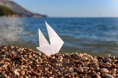 Bateau de papier sur une plage Image libre de droits