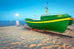 Bateau de pêche vert sur la plage de la mer baltique Photos stock