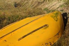 Bateau de rangée jaune retourné Photo stock
