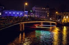 Bateau de ruise de ¡ de Ð avec la tache floue légère passant des canaux de nuit d'Amsterdam Image libre de droits