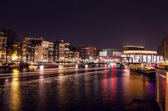 Bateau de ruise de ¡ de Ð avec la tache floue légère passant des canaux de nuit d'Amsterdam Photo stock