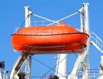Bateau de sauvetage rouge sur le levage de grue Image libre de droits
