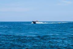 Bateau de vitesse emballé à travers la mer image stock