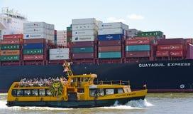 Bateau de voyage aller-retour près de navire porte-conteneurs images libres de droits