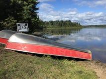 Bateau disponible pour la location par un lac calme Photographie stock