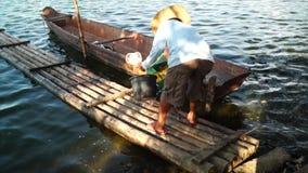 Bateau en bambou de radeau de vagabond d'embarquement de pêcheur sur le lac clips vidéos