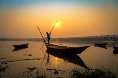 Bateau en bois avec le rameur au coucher du soleil sur la rivière Damodar Photographie stock libre de droits