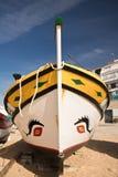 Bateau en bois coloré traditionnel vide attendant sur la plage sablonneuse en ciel bleu Photos stock