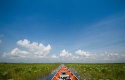 Bateau en bois de croisière dans le lac avec le fond nuageux de ciel bleu Images libres de droits