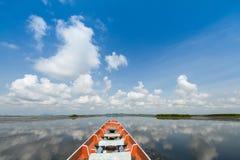 Bateau en bois de croisière dans le lac avec le fond nuageux de ciel bleu Image libre de droits