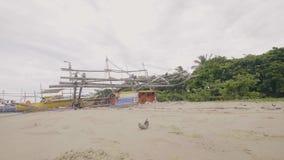 Bateau en bois de vieille navigation cassée sur la plage arénacée tropicale d'océan banque de vidéos