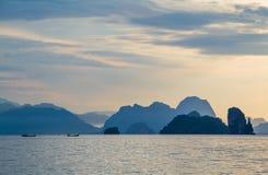Bateau en bois flottant sur la mer avec le petit fond de montagnes Photo stock