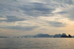 Bateau en bois flottant sur la mer avec le petit fond de montagnes Photos stock