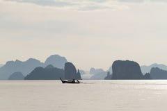 Bateau en bois flottant sur la mer avec le petit fond de montagnes Photographie stock libre de droits